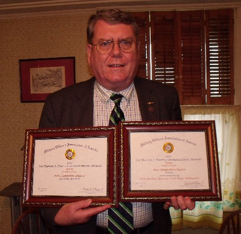 CDR McLean with award certificates